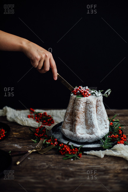 Woman slicing a holiday cake toped with powdered sugar and berries