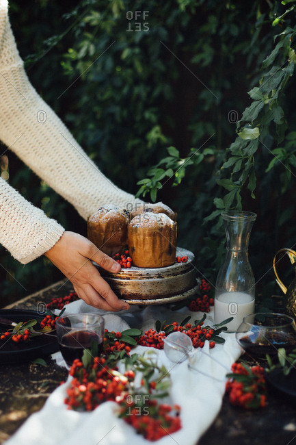 Woman placing holiday mini cakes on an outdoor table with berries