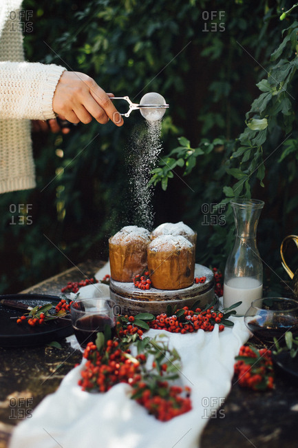 Woman dusting mini cakes with powdered sugar on an outdoor table