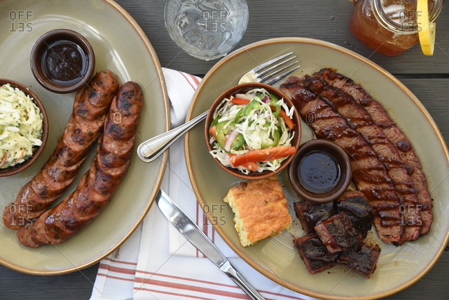 Meat served with salad, cornbread, and sauce