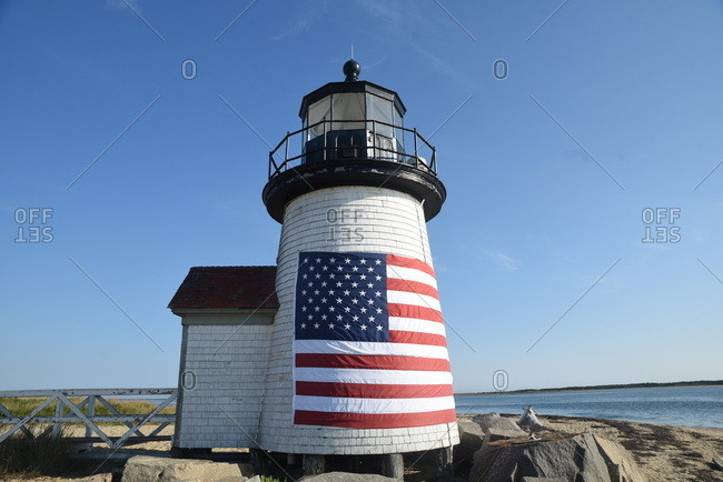 American flag hanging on exterior of lighthouse