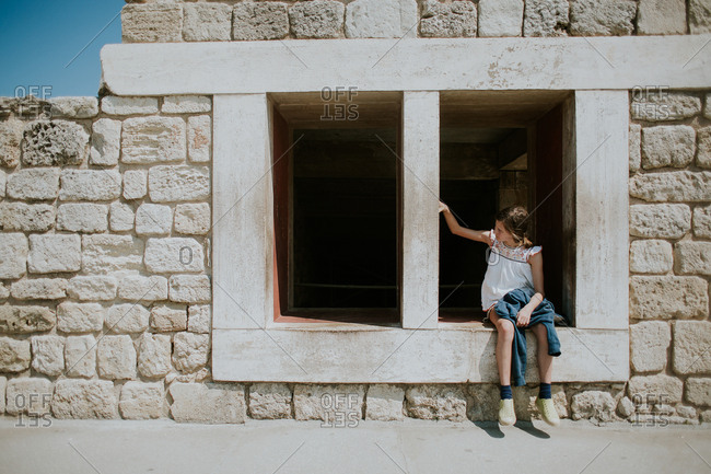 Girl sitting on window opening in ancient building on Crete