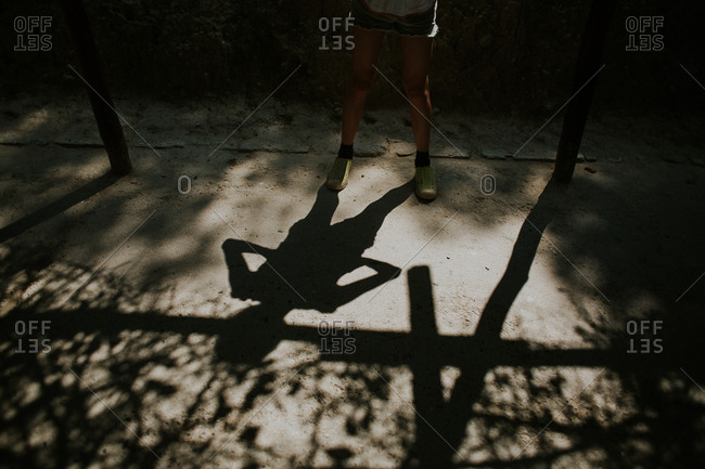 Shadow of a girl standing with her hands on her hips