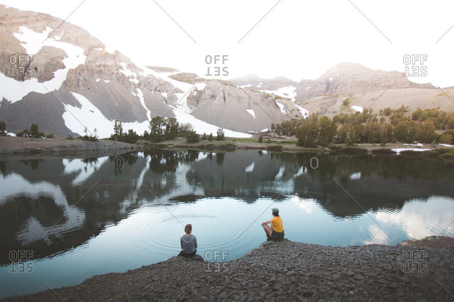 Two people sitting on the shore of a mountain lake