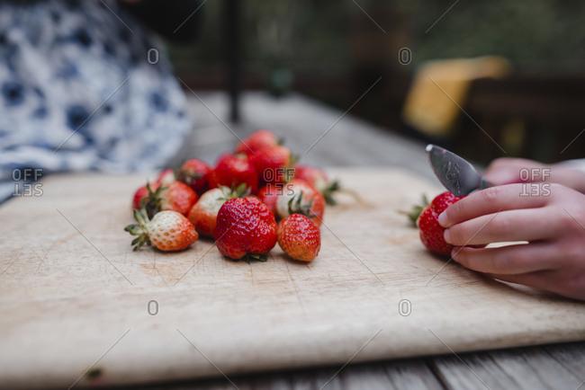 Cropped hands of girl cutting strawberry on cutting board at table