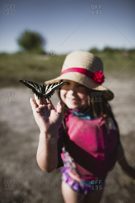 Girl holding butterfly while standing on field during summer