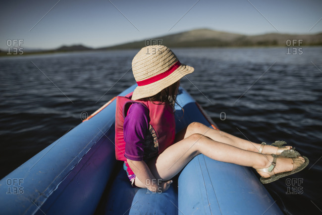 Side view of thoughtful girl wearing hat while sitting in inflatable raft on lake