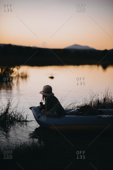 Girl sitting in inflatable raft on lake against clear sky during sunset