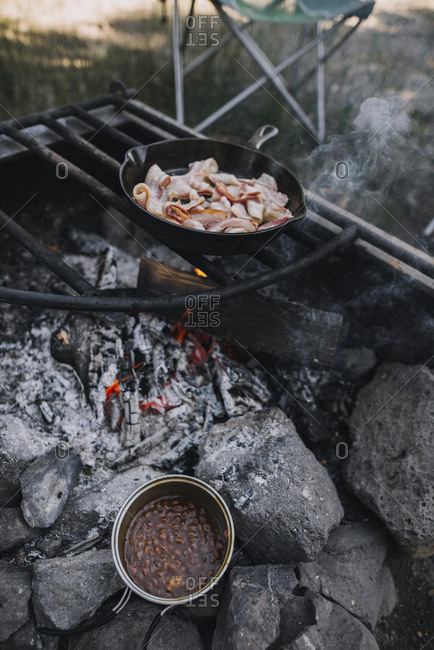 High angle view of bacon in skillet being cooked on open fire at campsite