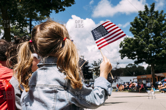 Rear view of girl holding American Flag during Independence Day