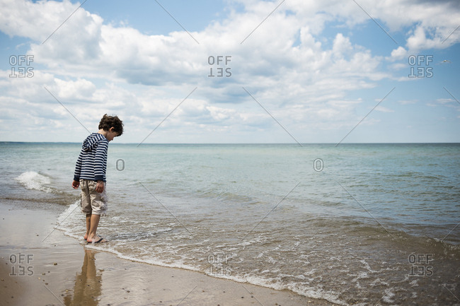 Full length of boy playing in waves at beach against cloudy sky
