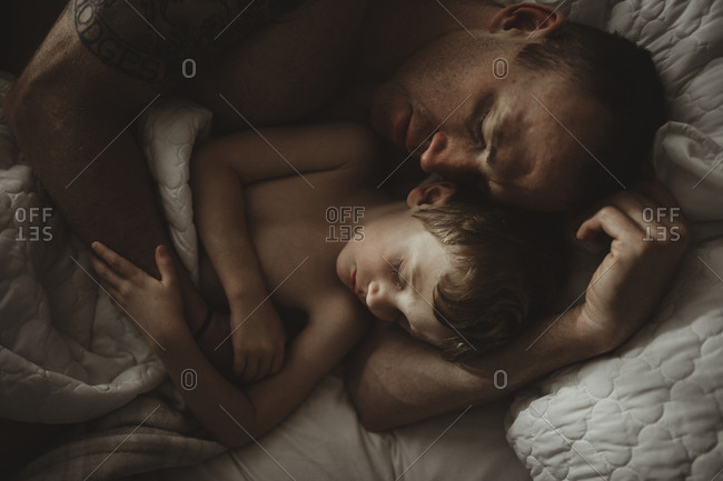 High angle view of father and son sleeping on bed