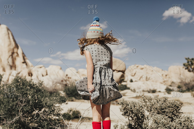 Rear view of girl with tousled hair standing against rock formations