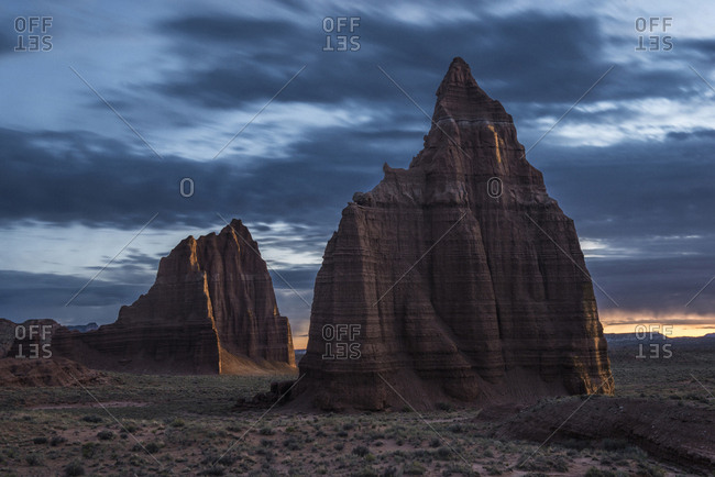Scenic view of rock formations at Capitol Reef National Park against cloudy sky during sunset