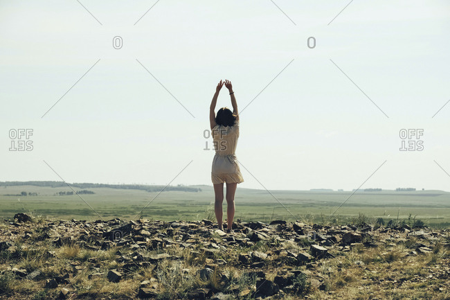Rear view of woman stretching while standing on rocky field against clear sky