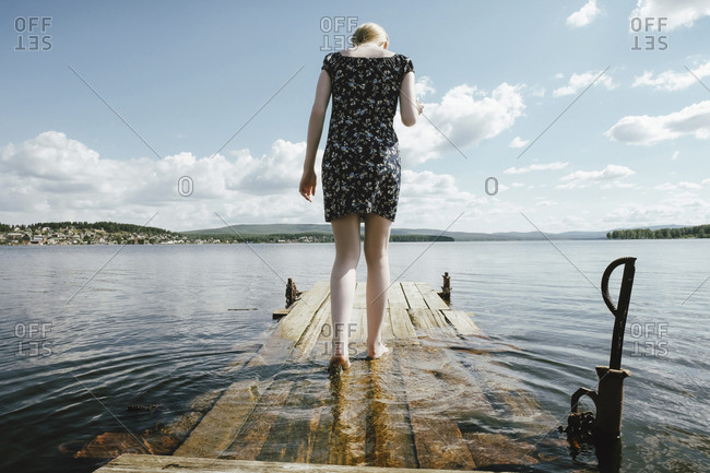 Rear view of woman walking on pier in river against cloudy sky