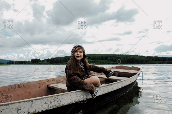 Girl looking away while sitting in rowboat on lake against cloudy sky