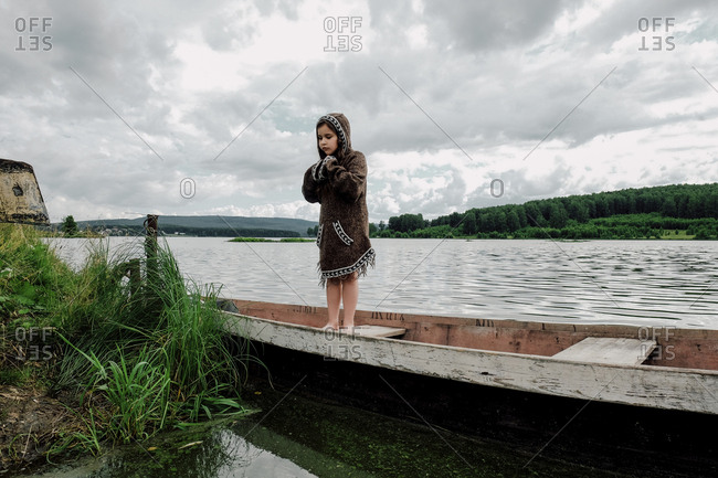 Girl wearing hooded jacket while standing in rowboat on lake