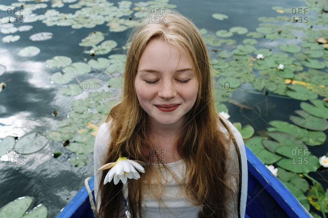 Close-up of happy woman with eyes closed sitting in boat on lake