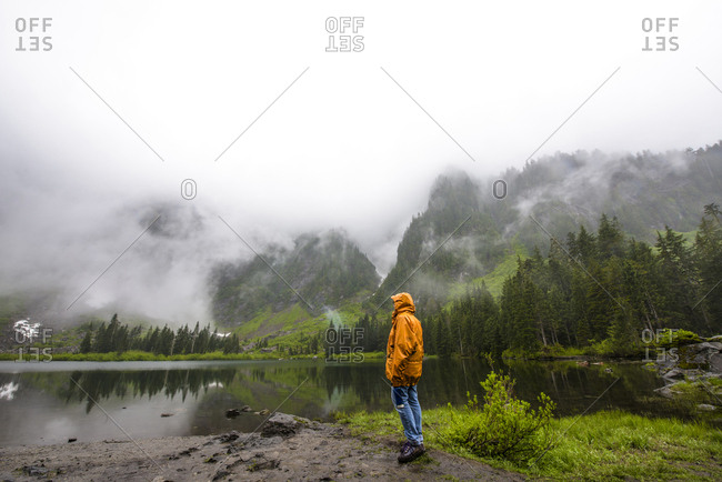 Full length of thoughtful woman wearing hooded jacket while standing by Heather Lake during foggy weather