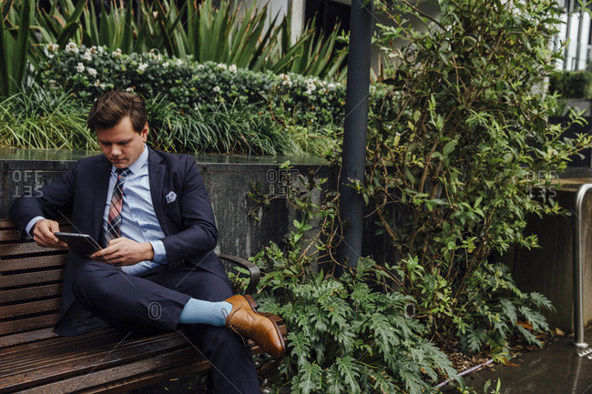Businessman using tablet computer while sitting on sidewalk bench