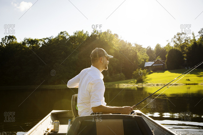Man fishing while sitting in rowboat on lake during sunny day