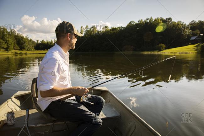 Man fishing while sitting in rowboat on lake