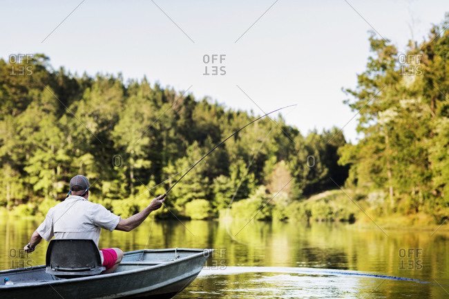 Rear view of man fishing while sitting in rowboat on lake against trees and sky