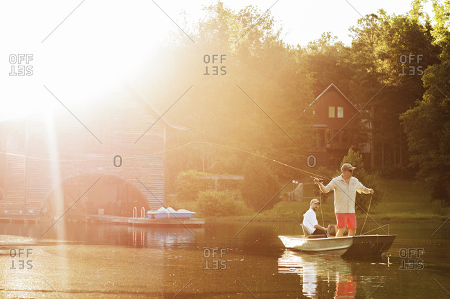 Man casting fishing line in lake with friend sitting in rowboat during sunny day