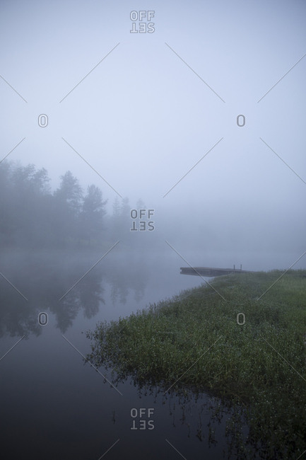Scenic view of lake by trees and sky during foggy weather