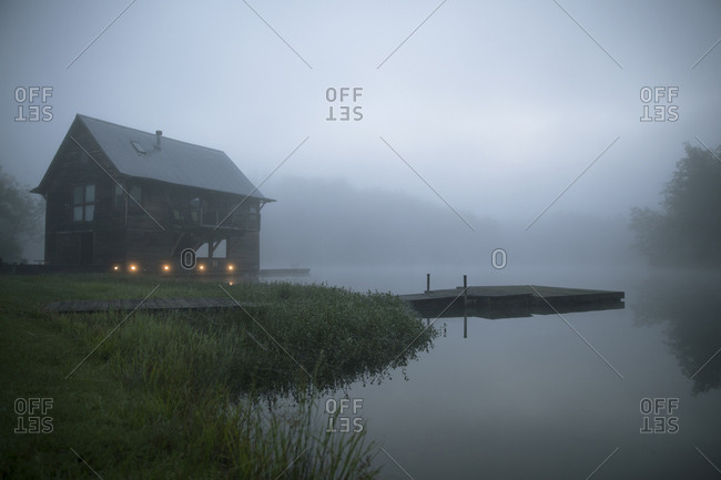 Log cabin at lakeshore during foggy weather