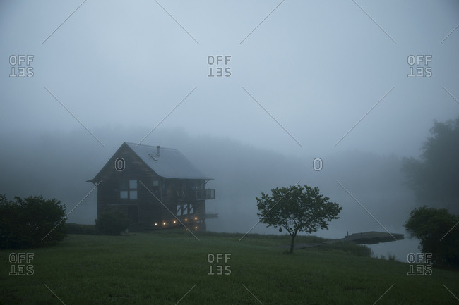 Log cabin at lakeshore against sky during foggy weather