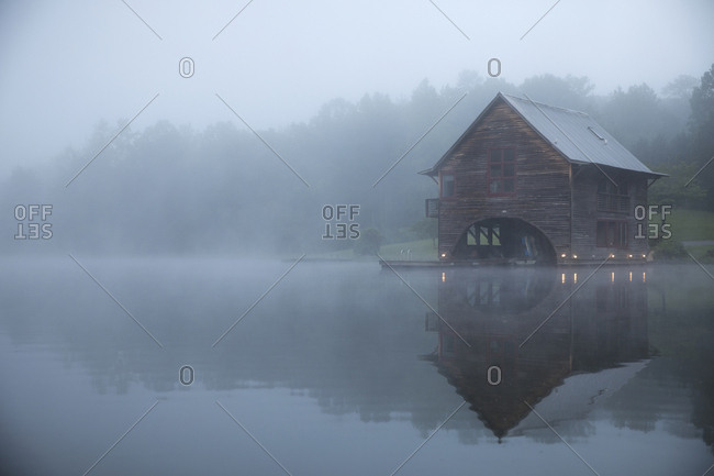 Symmetry view of log cabin by lake against trees during foggy weather