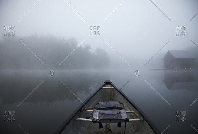 Boat in lake against sky during foggy weather