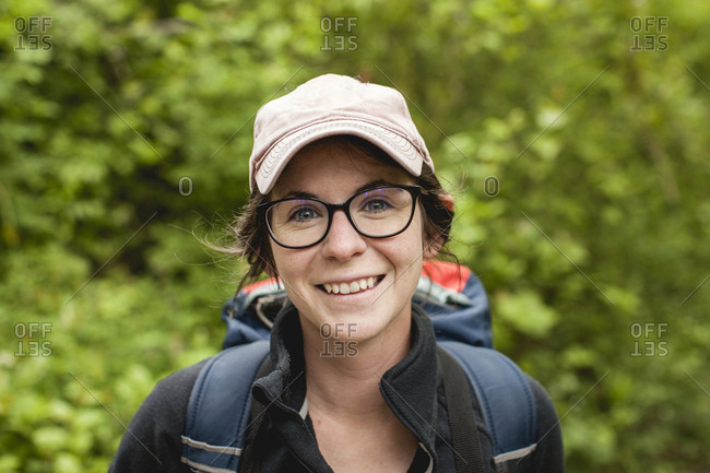 Close-up portrait of happy female hiker with backpack at Redwood National and State Parks
