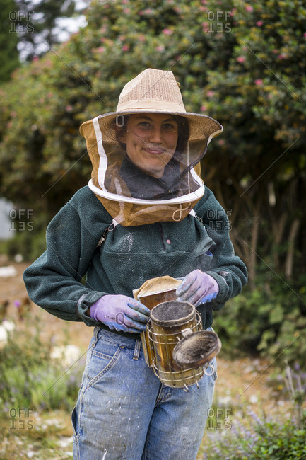 Portrait of female beekeeper wearing protective workwear while standing at farm