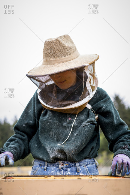 Female beekeeper working against clear sky at farm