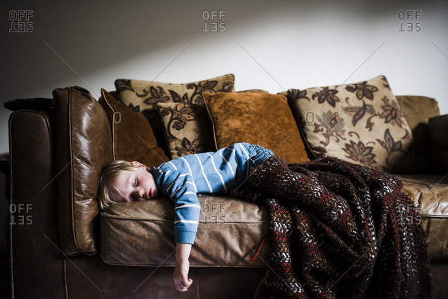 Boy sleeping on couch at home against wall
