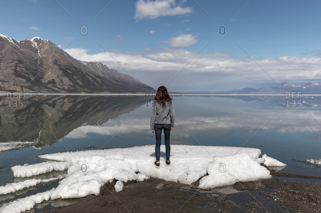 Woman standing on snow by river while looking at view against mountains and sky