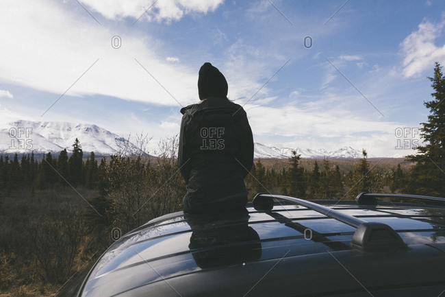 Rear view of thoughtful woman sitting on car roof at Denali National Park against snowcapped mountains