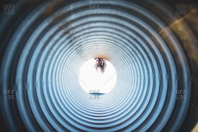 Playful girl peeking through tube at playground