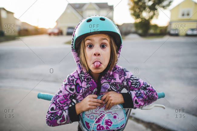 Portrait of playful girl sticking out tongue while riding push scooter on footpath