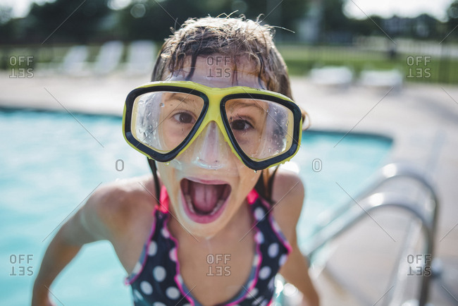 Portrait of girl with mouth open wearing swimming goggles while standing on poolside
