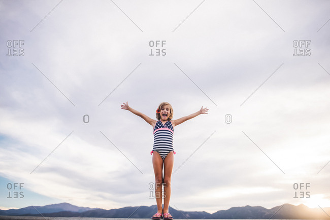Low angle view of girl with arms outstretched wearing swimwear while standing against cloudy sky