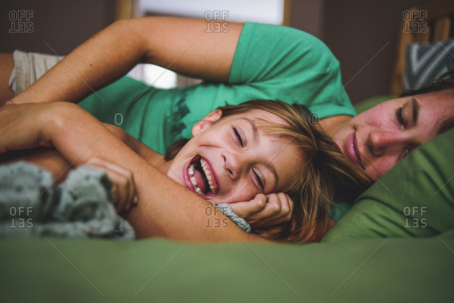 Cheerful daughter lying with sleeping mother on bed