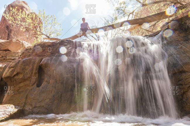 Low angle view of woman sitting on tree trunk over waterfall during sunny day