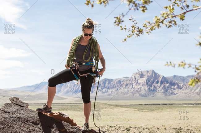 Full length of woman tightening safety harness while standing against mountains at Red Rock Canyon National Conservation Area