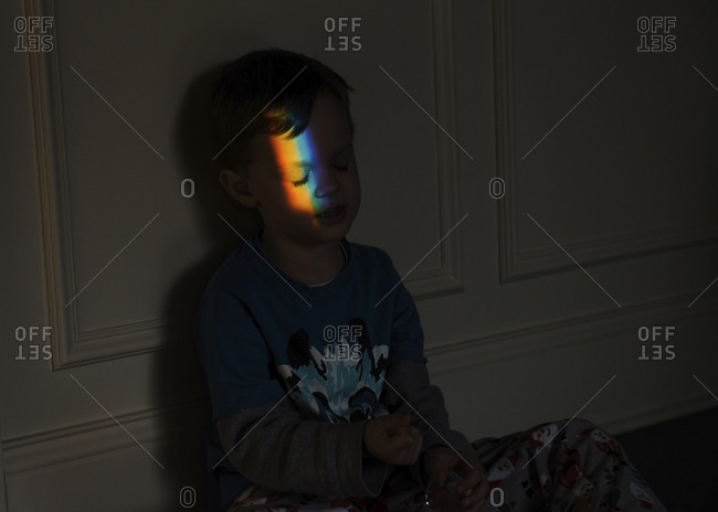Spectrum falling on boy's face while sitting in darkroom