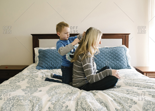 Cute son combing mother's hair while kneeling on bed against wall at home