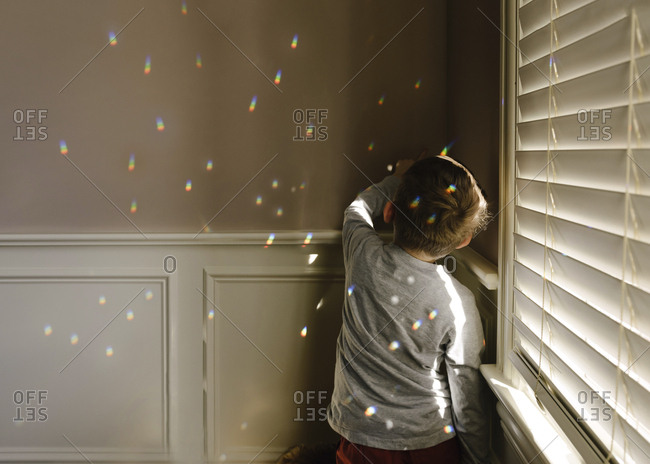 Boy playing with spectrum while standing by window